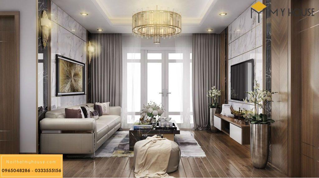 Chiếc sofa màu kem kết hợp hài hòa với chiếc bàn gỗ, thân rỗng, bề mặt bằng chất liệu giả đá sang trọng.